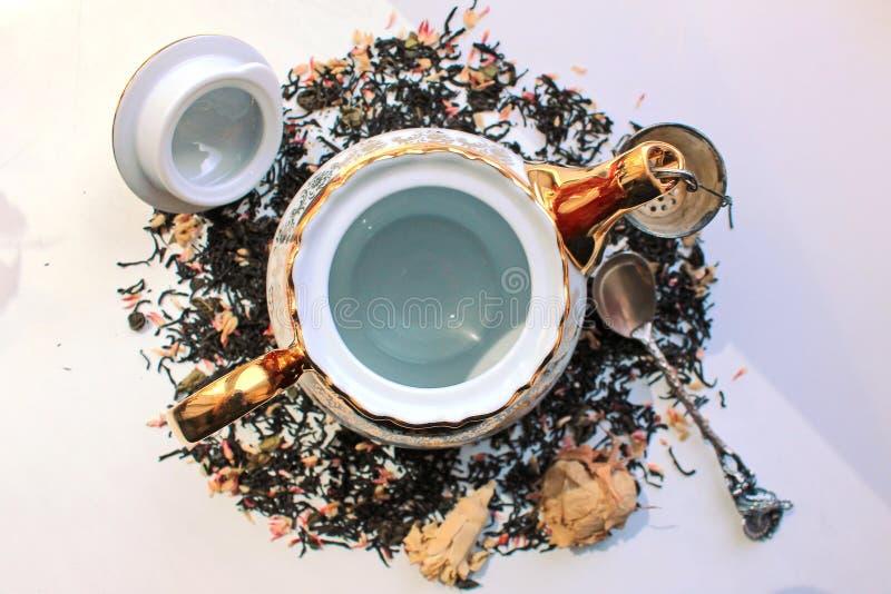 Πολύχρωμο teapot πορσελάνης και ασημένιο κουτάλι που περιβάλλονται από το τσάι χαλαρών φύλλων στο άσπρο υπόβαθρο στοκ εικόνες