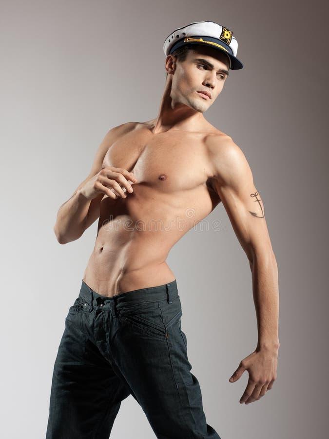 Πολύ ελκυστικός αρσενικός κορυφαίος γυμνός με έναν ναυτικό ΚΑΠ στοκ φωτογραφία