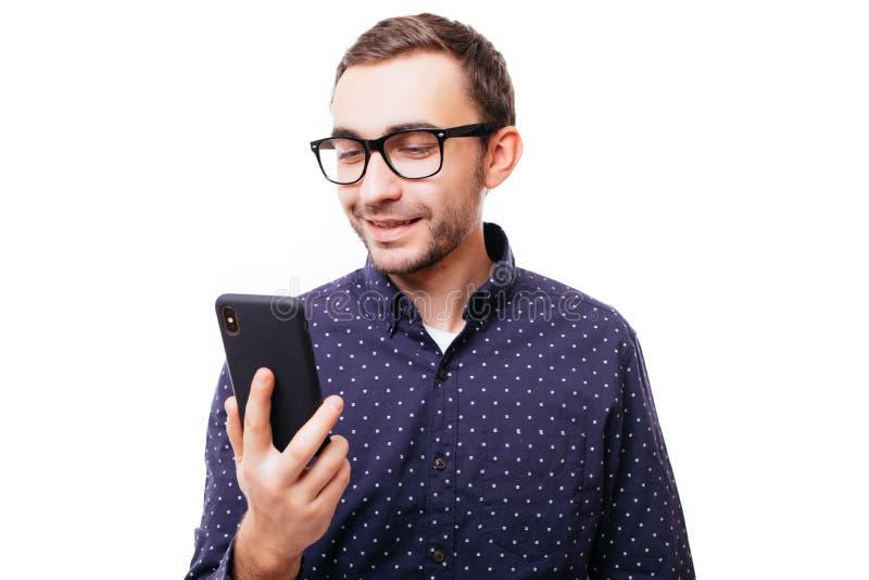 Πολύ ευτυχές χαμογελώντας νέο ενήλικο άτομο στο άσπρο πουκάμισο που εξετάζει το κινητό τηλέφωνό του στο άσπρο υπόβαθρο στοκ εικόνα με δικαίωμα ελεύθερης χρήσης