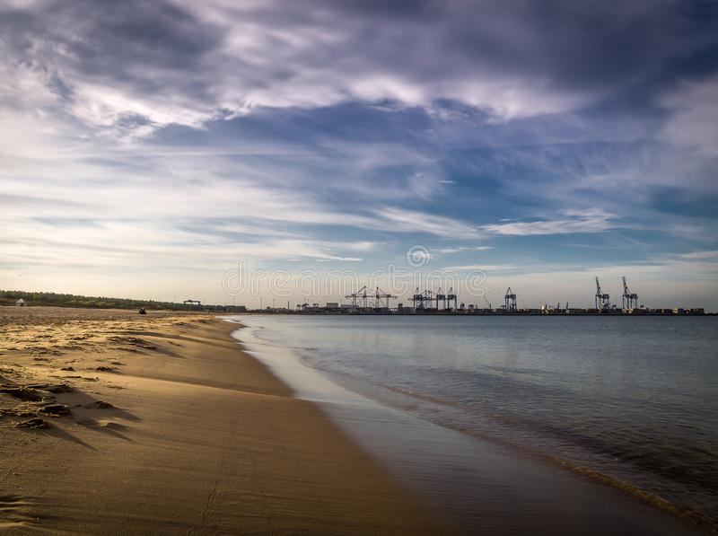 Πολύ κενή καθαρή παραλία Stogi άμμου στο Γντανσκ, Πολωνία με το ναυπηγείο του Στάλιν με τους γερανούς στο υπόβαθρο στοκ εικόνες
