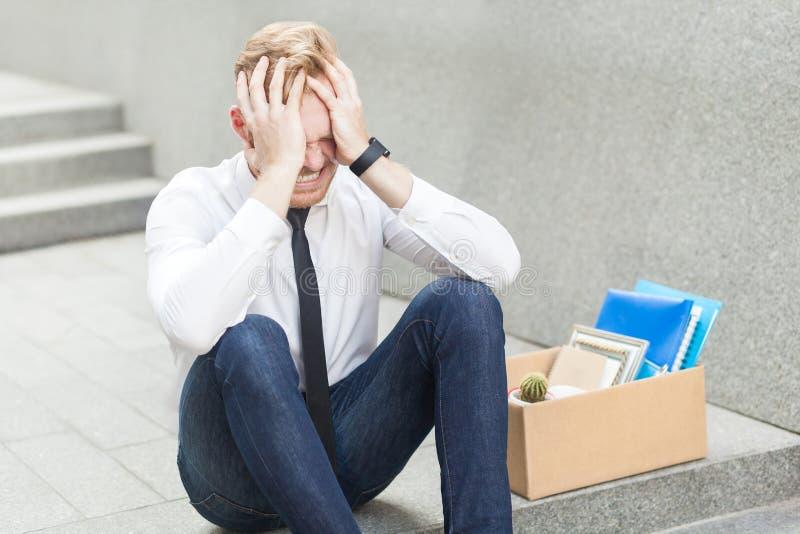 Πολύ λυπημένο κόκκινο επικεφαλής άτομο που απολύεται από την εργασία Δυστυχισμένο γενειοφόρο επιχειρησιακό άτομο που εγκαθιστούν  στοκ εικόνες