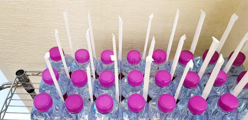 Πολύ πλαστικό μπουκάλι νερό με την πορφυρή μπουκάλι-ΚΑΠ και ο σωλήνας προετοιμάζονται για τον πελάτη υπηρεσιών στοκ φωτογραφίες