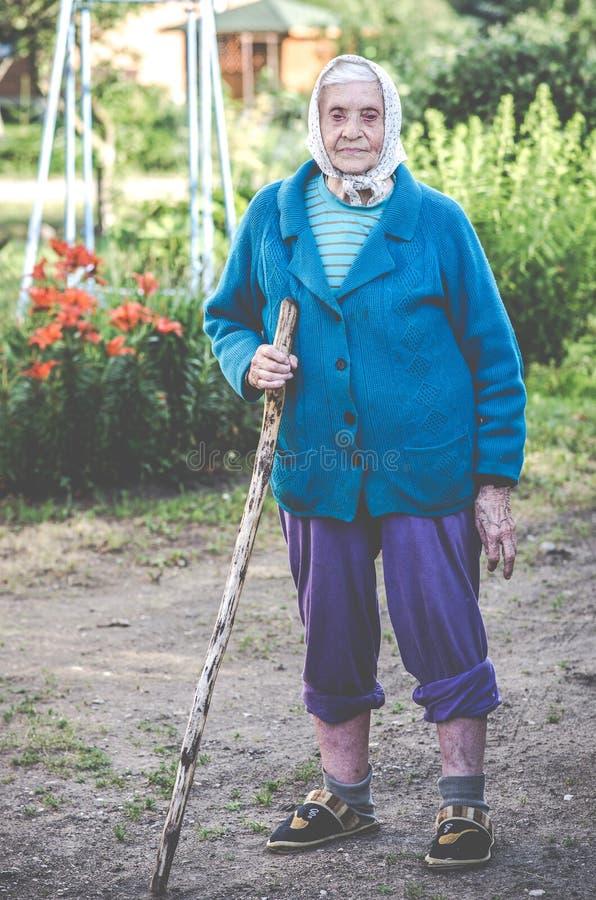 Πολύ στάση ηλικιωμένων γυναικών, που κρατά τον κάλαμο στοκ εικόνες