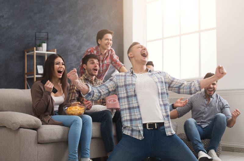Πολύ συγκινημένοι φίλοι που προσέχουν τον αγώνα ποδοσφαίρου στο σπίτι στοκ φωτογραφίες