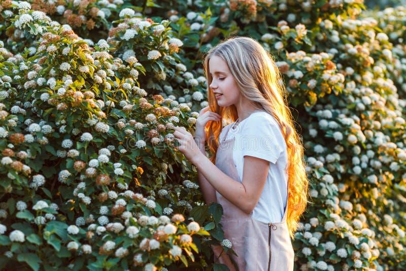 Πολύ χαριτωμένη έφηβη με λουλούδια σε ένα κόκκινο φόρεμα που ποζάρει στοκ εικόνες