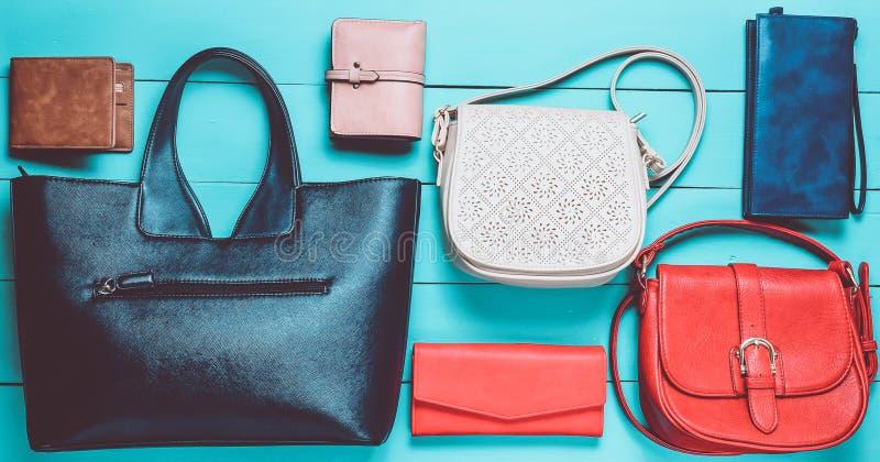 Πολύ women& x27 τσάντες και πορτοφόλια του s σε ένα μπλε ξύλινο υπόβαθρο Τοπ όψη στοκ εικόνες