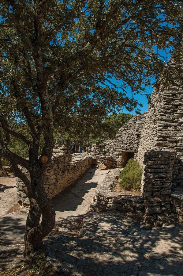 Πορεία και καλύβες φιαγμένες από πέτρα κάτω από τον ηλιόλουστο μπλε ουρανό, στο χωριό Bories, κοντά σε Gordes στοκ εικόνα