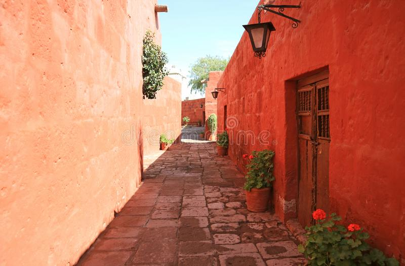 Πορεία κυβόλινθων μεταξύ των κόκκινων και πορτοκαλιών παλαιών κτηρίων χρώματος στο μοναστήρι Santa Catalina, Arequipa, Περού στοκ εικόνες