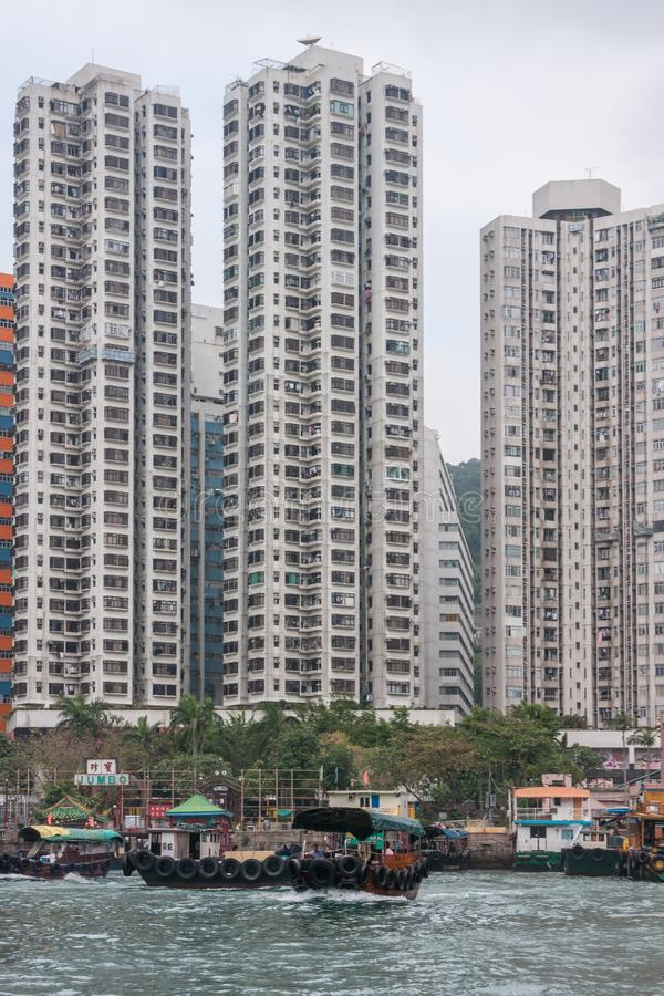 Πορθμείο Sampan μπροστά από τα ψηλά κτίρια στο λιμάνι του Χονγκ Κονγκ, Κίνα στοκ φωτογραφία