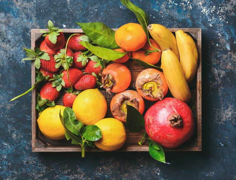 Πορτοκάλια, λεμόνια, ρόδι, μπανάνες, φράουλες και persimmon στο ξύλινο κιβώτιο στοκ εικόνες