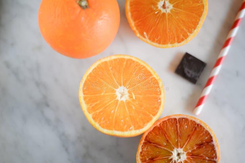 Πορτοκάλια που κόβονται στο μισό σε έναν μαρμάρινο πίνακα στοκ εικόνες