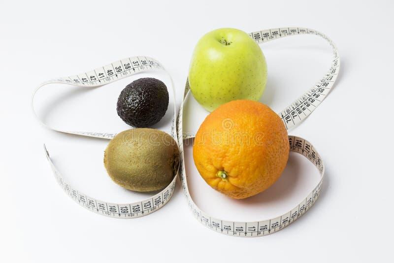 Πορτοκάλι, μήλο, ακτινίδιο και αβοκάντο που περιβάλλονται από ένα μέτρο ταινιών στοκ φωτογραφίες