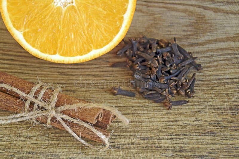 Πορτοκάλι, ραβδιά κανέλας, γαρίφαλα στο ξύλινο υπόβαθρο στοκ εικόνα