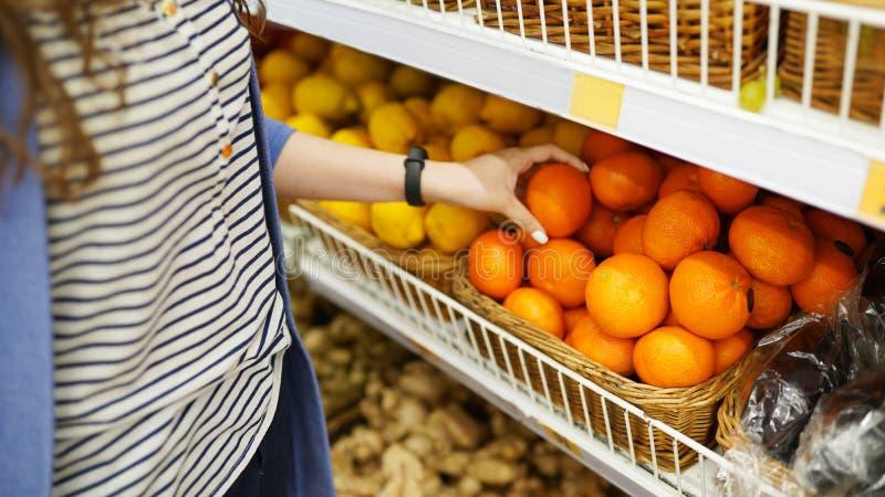 Πορτοκάλι στην αγορά το θηλυκό μαζεύει με το χέρι επάνω τους νωπούς καρπούς concept healthy lifestyle στοκ εικόνα