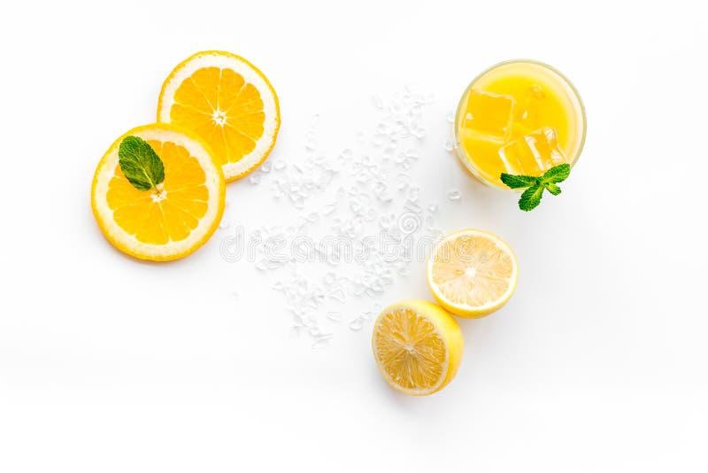 πορτοκάλι χυμού πάγου κύβ& Ο χυμός στο ποτήρι έκοψε πλησίον το πορτοκάλι και το λεμόνι, συντριμμένος πάγος, πράσινη μέντα στην άσ στοκ φωτογραφίες