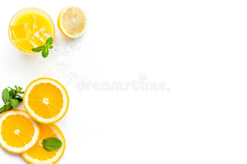 πορτοκάλι χυμού πάγου κύβ& Ο χυμός στο ποτήρι έκοψε πλησίον το πορτοκάλι και το λεμόνι, συντριμμένος πάγος, πράσινη μέντα στην άσ στοκ εικόνες