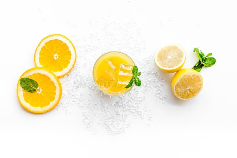πορτοκάλι χυμού πάγου κύβ& Ο χυμός στο ποτήρι έκοψε πλησίον το πορτοκάλι και το λεμόνι, συντριμμένος πάγος, πράσινη μέντα στην άσ στοκ φωτογραφία με δικαίωμα ελεύθερης χρήσης