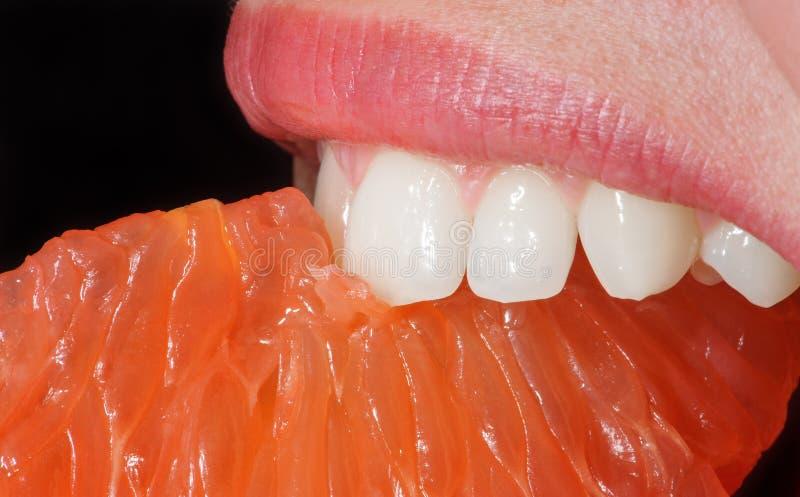 Πορτοκάλι κινηματογραφήσεων σε πρώτο πλάνο στο στόμα γυναικών ` s στοκ εικόνες