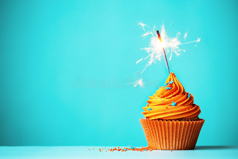 Πορτοκάλι cupcake με το sparkler στοκ εικόνες με δικαίωμα ελεύθερης χρήσης