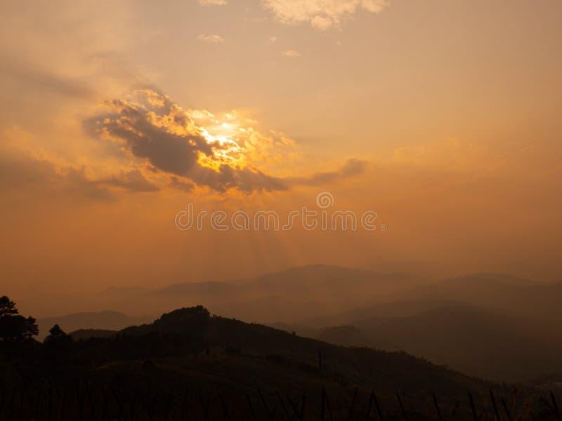 Πορτοκαλής και κίτρινος με τον ουρανό σύννεφων Ο ήλιος είναι κάτω το καλοκαίρι Είναι λυκόφως με το βουνό Είναι όμορφες σκηνή και  στοκ εικόνες