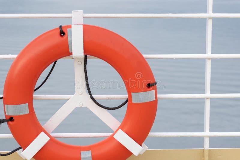 Πορτοκαλής lifebuoy εξοπλισμός συσκευών εργαλείων έκτακτης ανάγκης με τις αντανακλαστικές ασημένιες λουρίδες στη γέφυρα κρουαζιερ στοκ φωτογραφία