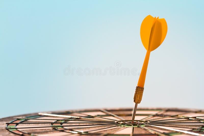 Πορτοκαλί βέλος βελών που χτυπά το ταύρος-μάτι στο κέντρο του dartboard στο υπόβαθρο μπλε ουρανού στοκ εικόνα