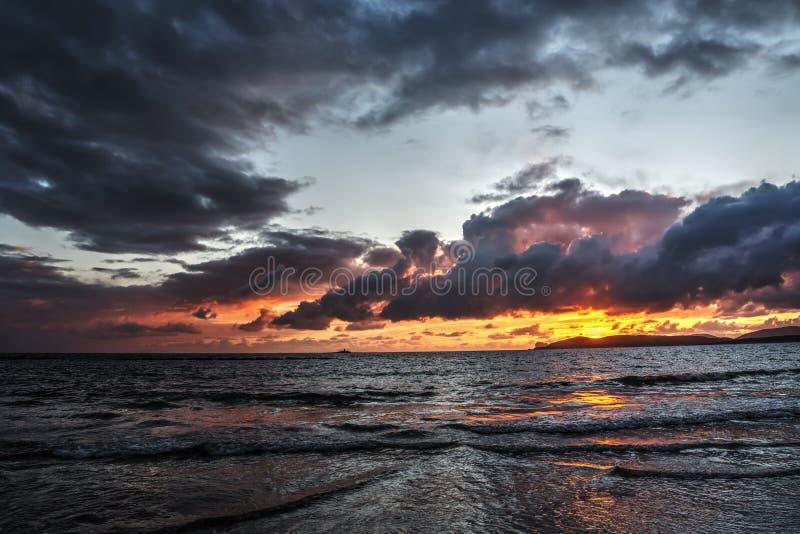 Πορτοκαλί και μαύρο ηλιοβασίλεμα στην παραλία στοκ εικόνες