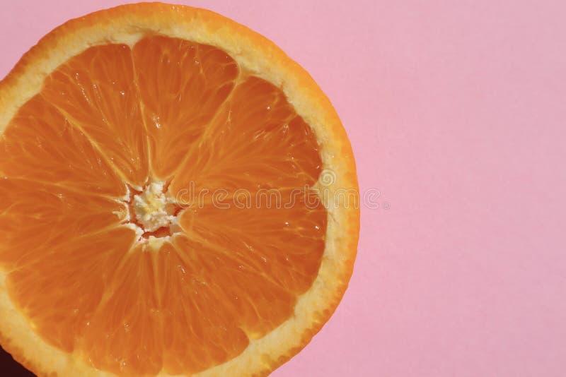 Πορτοκαλί μισό σε χλωμό - ρόδινο υπόβαθρο στοκ εικόνες