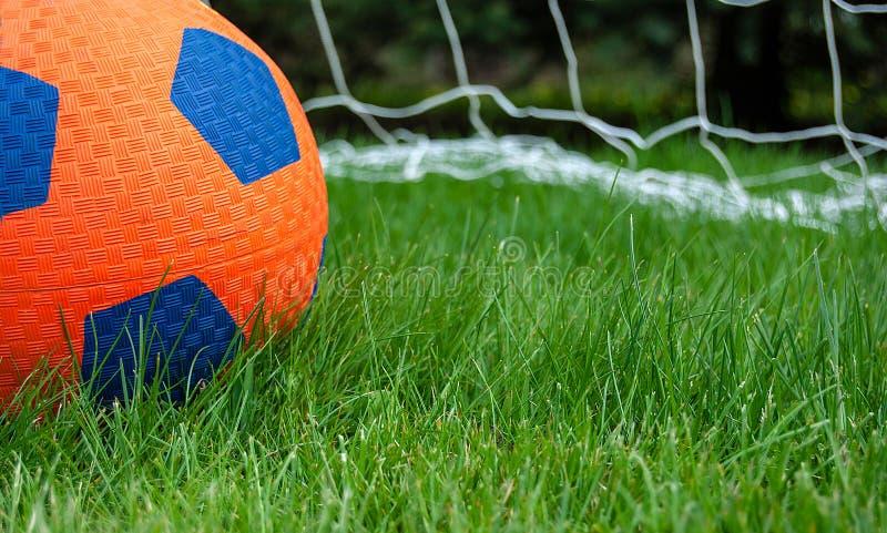 Πορτοκαλί μπάλα ποδοσφαίρου στο γήπεδο με δίχτυ στοκ φωτογραφία με δικαίωμα ελεύθερης χρήσης