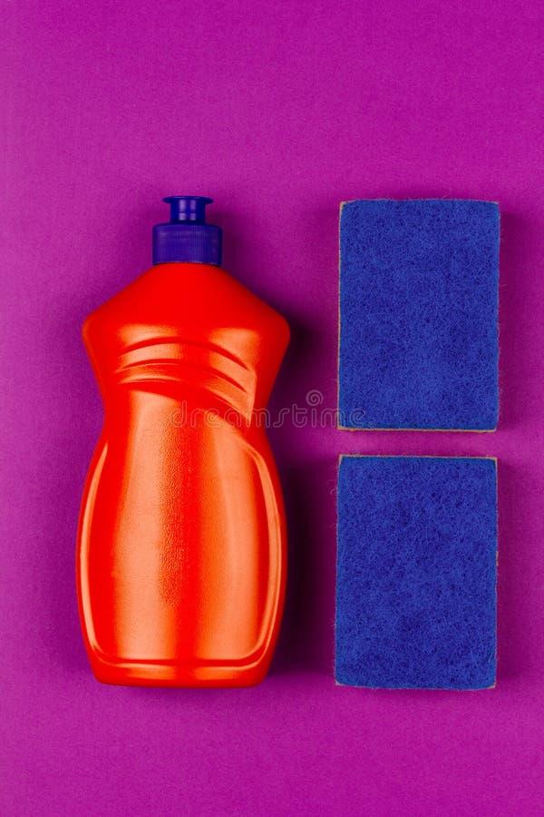 Πορτοκαλί πλαστικό μπουκάλι του υγρού και μπλε σφουγγαριού πλυσίματος των πιάτων στην πορφυρή κινηματογράφηση σε πρώτο πλάνο υποβ στοκ φωτογραφίες με δικαίωμα ελεύθερης χρήσης