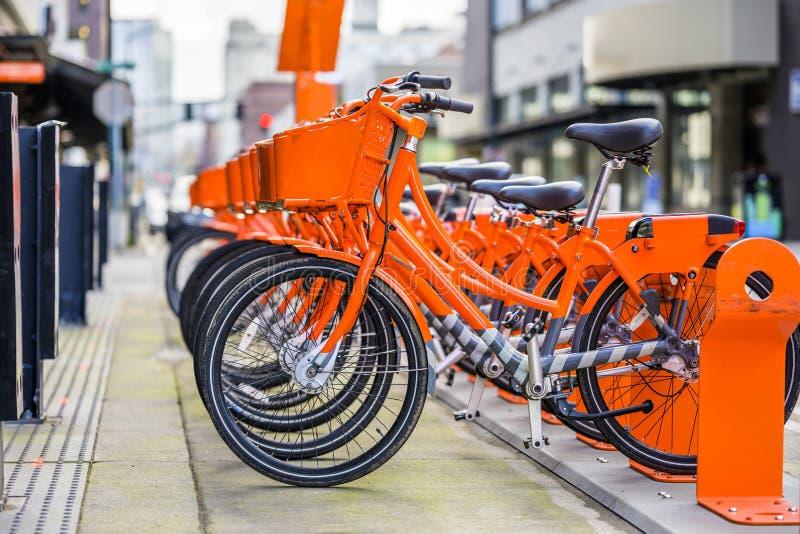 Πορτοκαλί ποδήλατα με καλάθια στη σειρά, περιμένοντας τους ποδηλάτες να νοικιάσουν ένα ποδήλατο και να ταξιδέψουν στην πόλη στοκ φωτογραφίες
