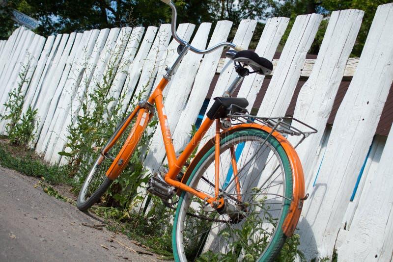 Πορτοκαλί ποδήλατο από το φράκτη στοκ φωτογραφίες