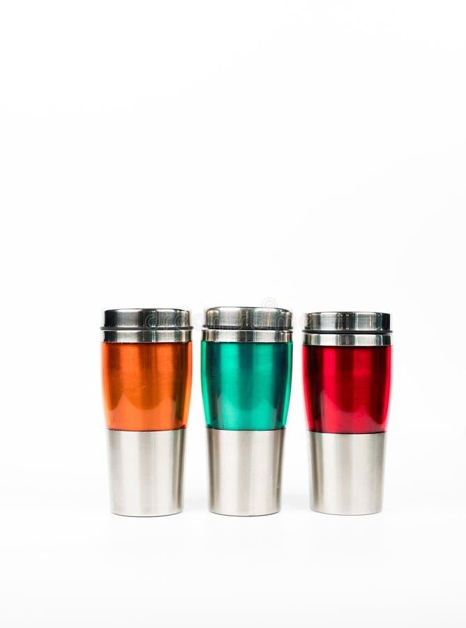 Πορτοκαλί, πράσινο και κόκκινο μπουκάλι thermos στο άσπρο υπόβαθρο στοκ εικόνες