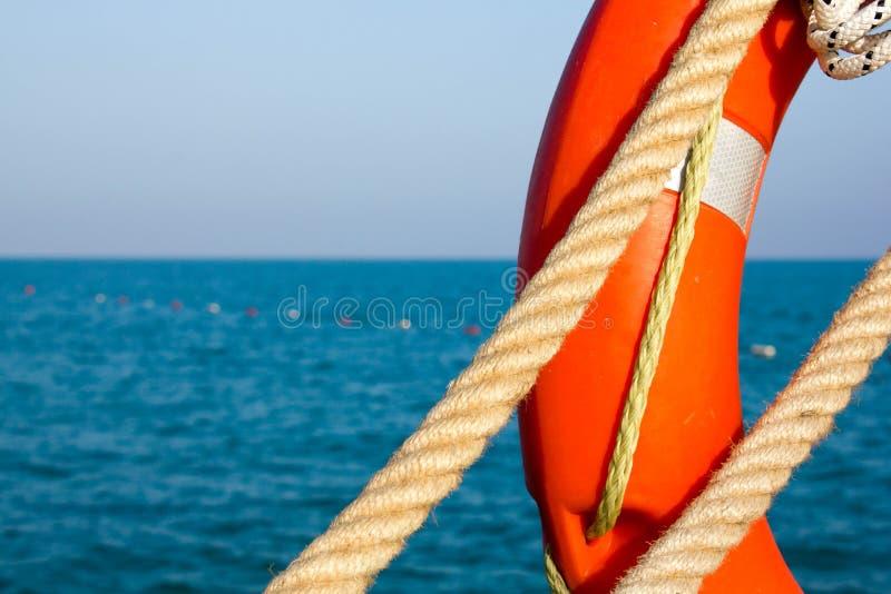 Πορτοκαλί συντηρητικό ζωής και θαλάσσιο σχοινί δύο στο υπόβαθρο της μπλε θάλασσας και του ουρανού o Lifebuoy στο υπόβαθρο της θάλ στοκ φωτογραφία με δικαίωμα ελεύθερης χρήσης