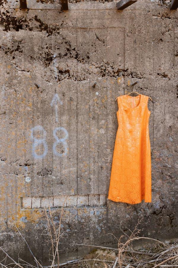 Πορτοκαλί φόρεμα με το χρυσό νήμα στην πτώση κάτω από τον τοίχο στοκ φωτογραφία με δικαίωμα ελεύθερης χρήσης