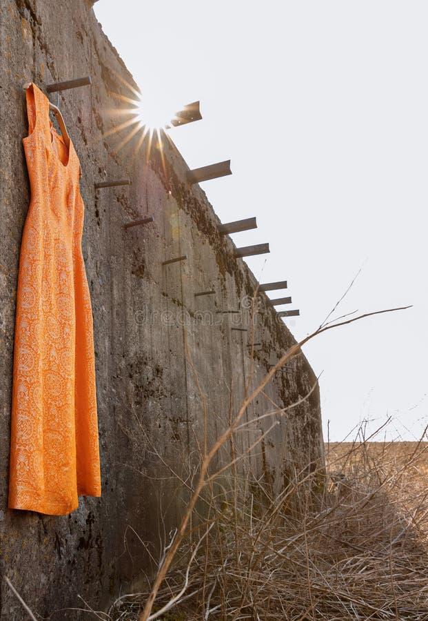 Πορτοκαλί φόρεμα με το χρυσό νήμα στην πτώση κάτω από τον τοίχο στοκ εικόνες