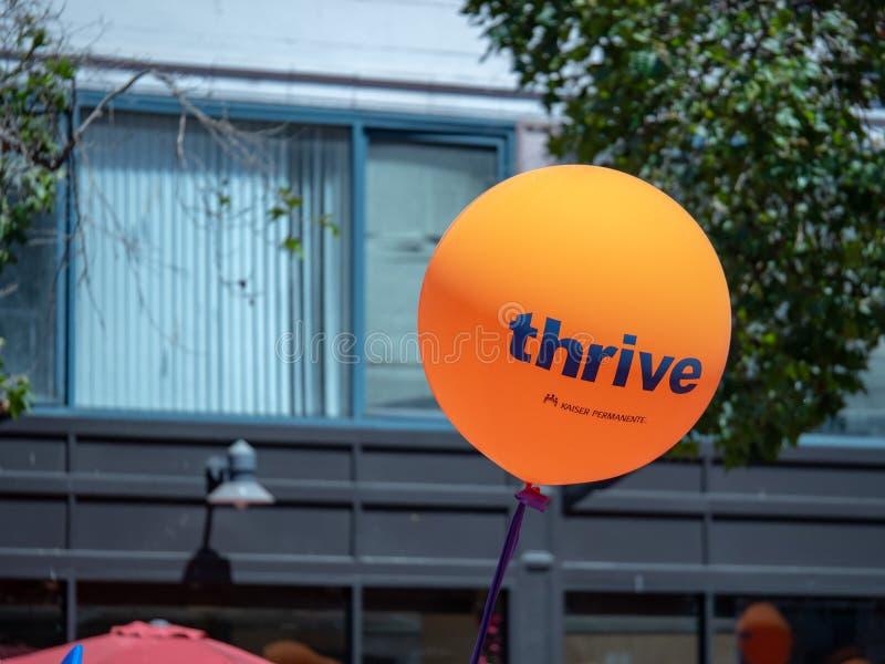 Πορτοκαλί Kaiser Permanente αναπτύσσεται μπαλόνι που πετά σε μια αστική περιοχή στοκ φωτογραφίες με δικαίωμα ελεύθερης χρήσης