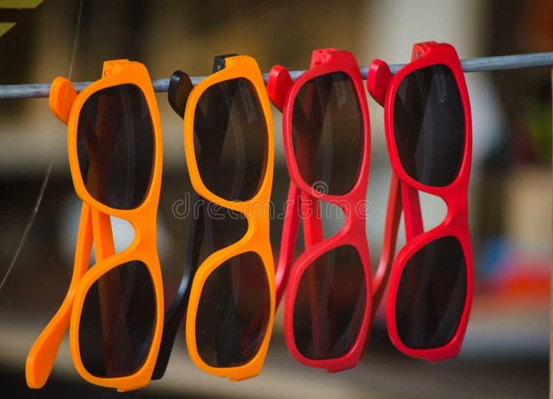 Πορτοκαλιά και κόκκινα φανταχτερά γυαλιά ηλίου που κρεμούν στην επίδειξη καταστημάτων στοκ εικόνες με δικαίωμα ελεύθερης χρήσης