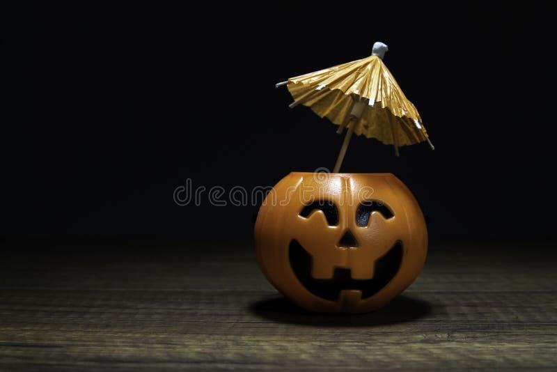 Πορτοκαλιά κολοκύθα αποκριές με την ομπρέλα στον ξύλινο πίνακα στο μαύρο υπόβαθρο στοκ φωτογραφία με δικαίωμα ελεύθερης χρήσης