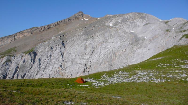 Πορτοκαλιά σκηνή σε ένα μακρινό και άγριο τοπίο βουνών με τα πράσινα λιβάδια και τις δύσκολες αιχμές κάτω από έναν μπλε ουρανό στοκ φωτογραφία με δικαίωμα ελεύθερης χρήσης