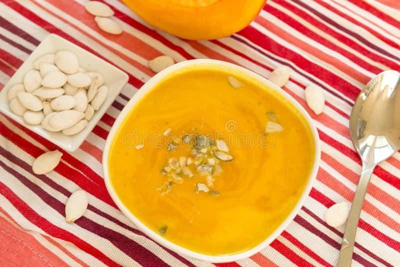 Πορτοκαλιά σούπα κολοκύθας σε ένα πιάτο, σπόροι κολοκύθας, κόκκινο ριγωτό τραπεζομάντιλο, κουτάλι στοκ εικόνα
