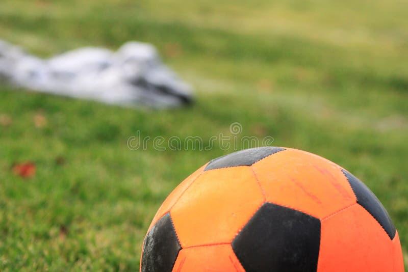 Πορτοκαλιά σφαίρα ποδοσφαίρου ποδοσφαίρου, πράσινος τομέας χλόης κλείστε επάνω στοκ εικόνες