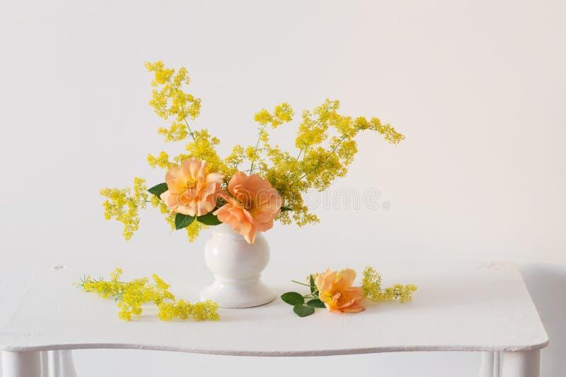 Πορτοκαλιά τριαντάφυλλα με τα άγρια λουλούδια στην ανθοδέσμη στο βάζο σε διά στοκ φωτογραφία με δικαίωμα ελεύθερης χρήσης