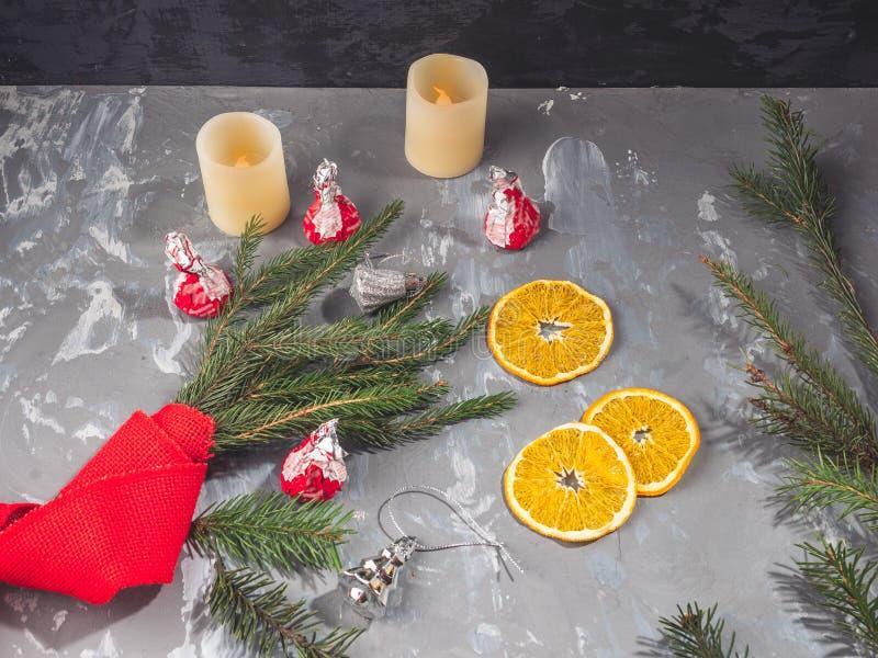 Πορτοκαλιά τσιπ δίπλα στους κλάδους των ερυθρελατών, που τυλίγονται με τα κόκκινα διακοσμητικά παιχνίδια Lenka και Χριστουγέννων στοκ φωτογραφίες με δικαίωμα ελεύθερης χρήσης
