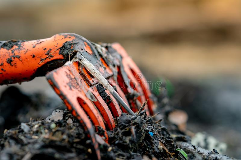 Πορτοκαλιά τσουγκράνα κινηματογραφήσεων σε πρώτο πλάνο στο σωρό των βρώμικων πλαστικών αποβλήτων στο θολωμένο υπόβαθρο Καθαρά επά στοκ φωτογραφίες