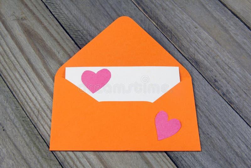 Πορτοκαλής φάκελος επιστολών αγάπης με την καρδιά εγγράφου στην κενή κάρτα στοκ φωτογραφίες