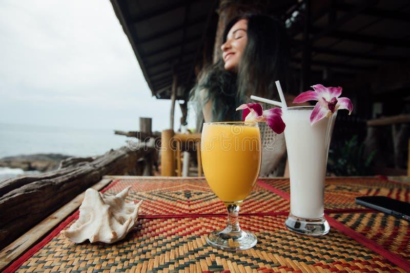 Πορτοκαλής χυμός μάγκο σε ένα γυαλί με ένα λουλούδι δίπλα σε ένα κοχύλι θάλασσας στο πρώτο πλάνο στοκ φωτογραφία με δικαίωμα ελεύθερης χρήσης