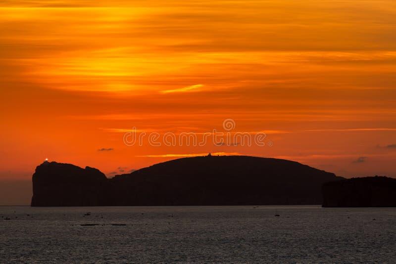 Πορτοκαλί ηλιοβασίλεμα πέρα από Capo Caccia και φάρος στη Σαρδηνία στοκ εικόνες