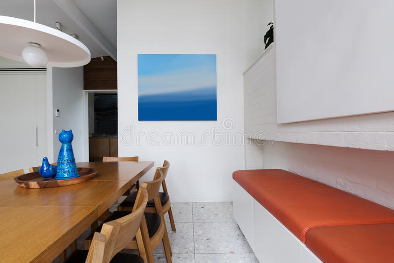 Πορτοκαλί κάθισμα πάγκων δέρματος κατά μήκος της Σκανδιναβικής ορισμένης τραπεζαρίας στοκ φωτογραφία με δικαίωμα ελεύθερης χρήσης