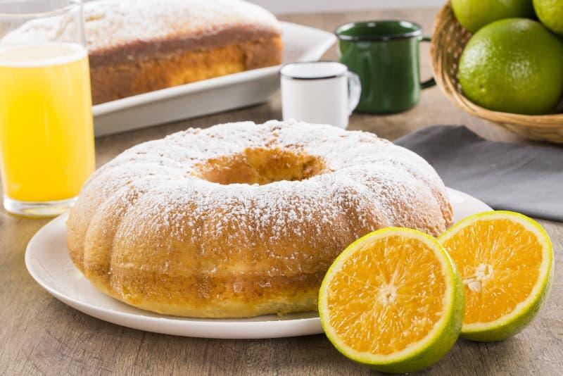 Πορτοκαλί κέικ στον πίνακα με τα φρούτα και το χυμό στοκ φωτογραφίες